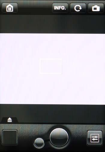 """Tryb Live View EOSa 70D w aplikacji EOS Remote. Po środku """"celownika"""" widzimy ustawianą dotykiem panelu smartfona ramkę ostrości – domyślnie jej wybór powoduje wyostrzenie obrazu i wyzwolenie migawki. Na dole mamy duży """"spust migawki"""" i towarzyszący mu opcjonalnie (menu ustawień) mniejszy """"przycisk"""" służący do automatycznego nastawiania ostrości. W kwadracie po lewej wyświetla się właśnie zrobione zdjęcie, a większa ich liczba – po jego dotknięciu – na pasku powyżej. Stąd mamy bezpośredni dostęp do wykonywanych zdjęć, także ich powiększeń (gestami smartfonowymi), bez wchodzenia do trybu odtwarzania. Kwadratem z prawej wyświetlamy dobierane z panelu parametry zdjęciowe, a przyciskiem INFO – podstawowe informacje o zdjęciach. Ikonka z symbolem aparatu (na górze z prawej) aktywuje bądź wyłącza tryb Live View, a ta z symbolem domu (z lewej) wywołuje ekran startowy aplikacji."""