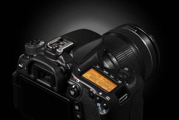 Tryb nagrywania filmów dostępny jest bezpośrednio – za pośrednictwem znanego z flagowego EOSa 7D przełącznika przy wizjerze. Znajdującym się poniżej przyciskiem Q wywołujemy ekran szybkich nastaw. Z jego poziomu można błyskawicznie aktywować wcześniej skonfigurowane połączenie Wi-Fi (na przykład ze smartfonem). Praca bezprzewodowa sygnalizowana jest na podświetlanym, górnym panelu LCD – migotaniem symbolu antenki. To dobrze, bo gdy zapomnimy o dezaktywacji  Wi-Fi, aparat dodatkowo zużyje nam energię akumulatora – nawet w trybie uśpienia stracimy jakieś 2% pojemności w ciągu każdej godziny. Przy sankach dla lampy błyskowej widać prawy z symetrycznie rozmieszczonej tam pary mikrofonów stereofonicznych.